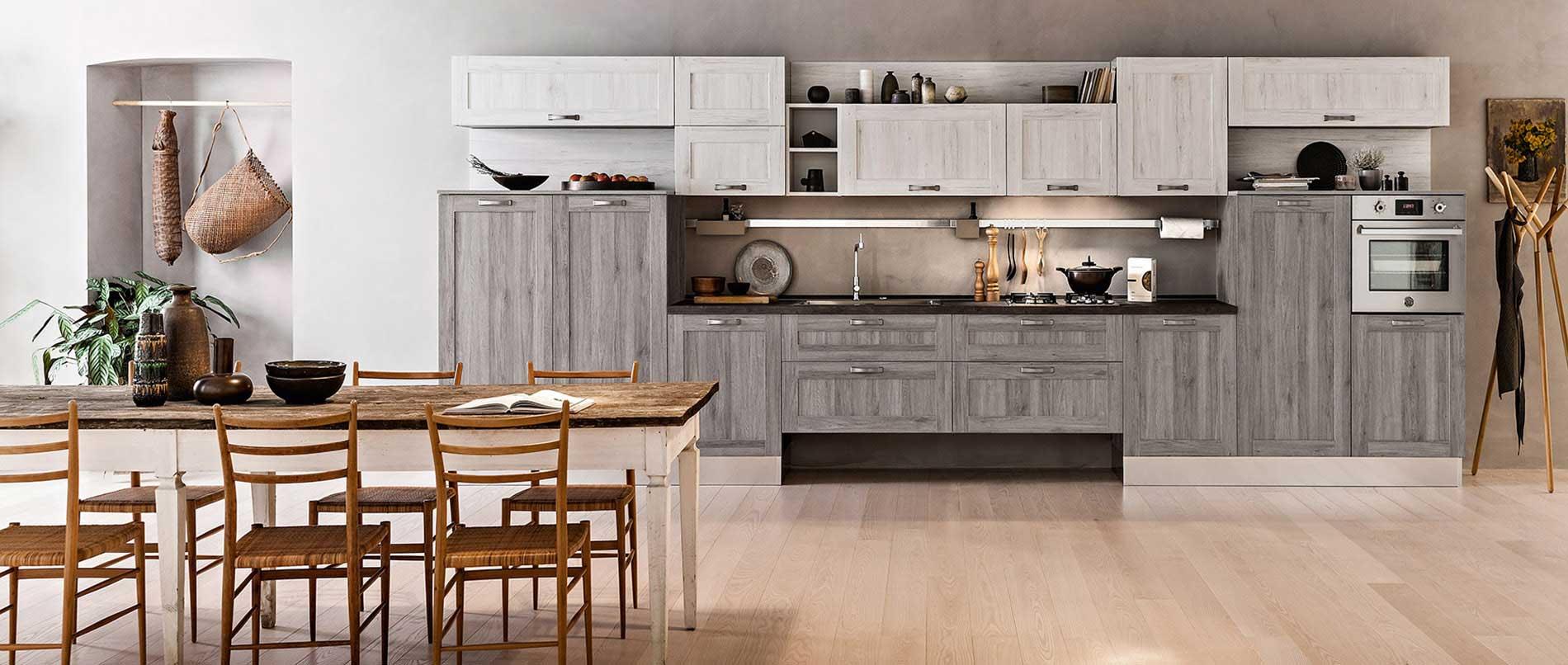 Cuisine déstructurée et équilibrée style vintage, accentué par le choix des façades effet bois chêne gris et blanc, les socles, la crédence en aluminium, et le jeu des niches.
