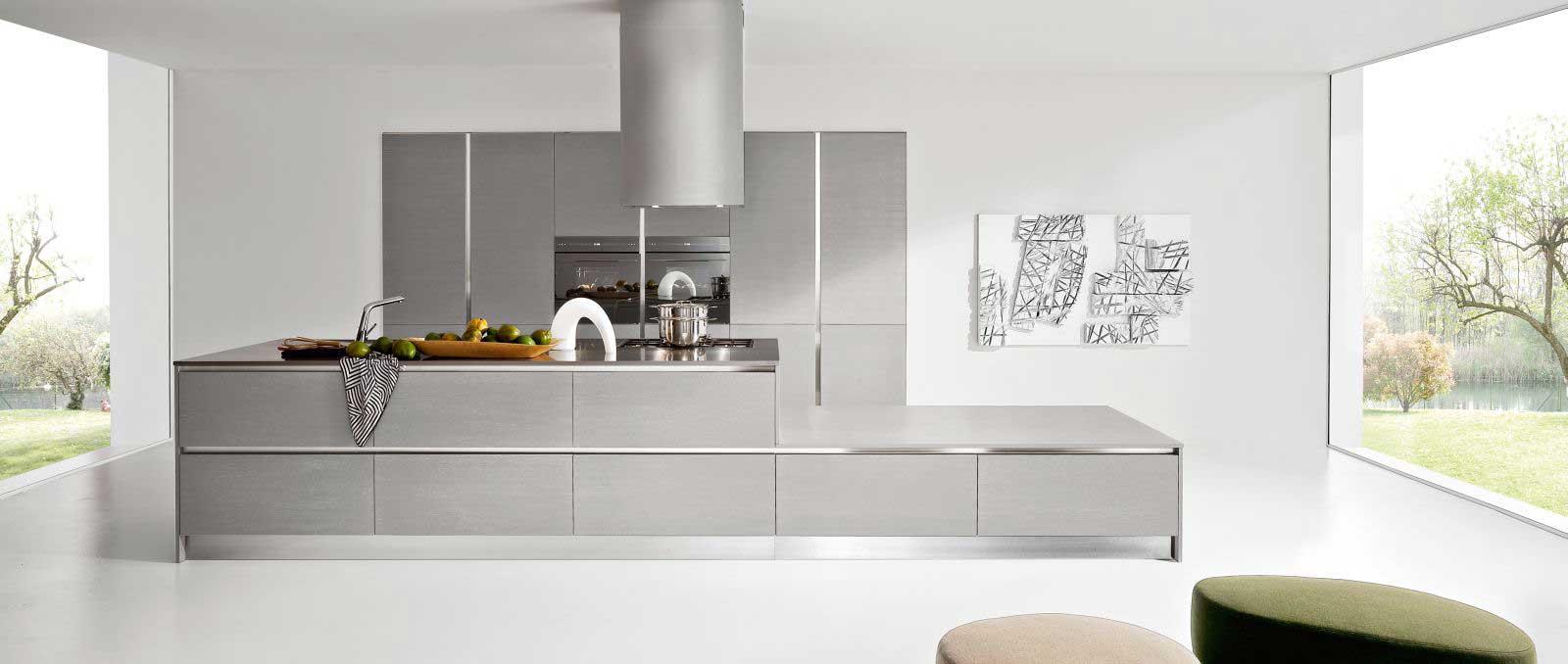 La beauté de cette cuisine est dans le détail, les finitions et accessoires. L'îlot avec coffre, les colonnes en laque gris Cendre, les profilés et socle en aluminium, le plan de travail en inox.
