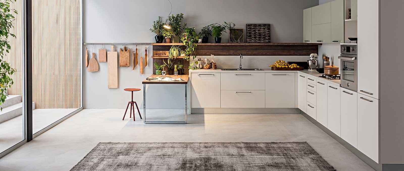 Le classique revisité, pour cette cuisine mariant demi-îlot, crédences en noyer vintage et façade de portes en laque mate blanc et gravier. Un espace pour cuisiner et vivre au quotidien.