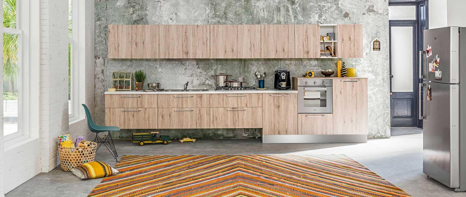 Cuisine équipée en linéaire, traditionnelle tout en étant très moderne avec ses meubles suspendus, ses demi-colonnes et poignées longues. Façades effet chêne Bronze.