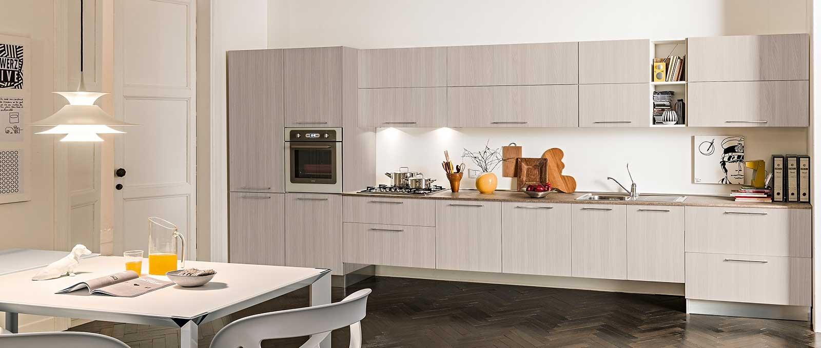 Cuisine linéaire au design à l'italienne, avec meubles suspendus, poignées horizontales et fil de bois vertical.