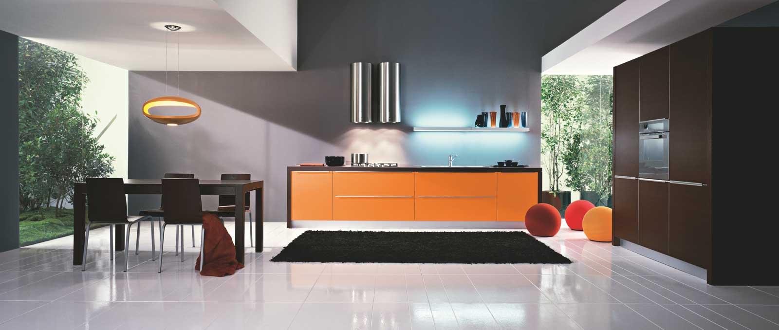 Sobre, épurée l'originalité de cette cuisine est dans la couleur et les retours de plan de travail qui lui donne une tendance très jeune et moderne. Façades orange mat et tabac.